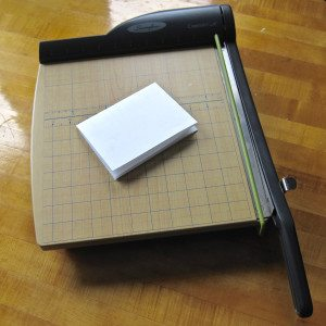 photo of paper folded in quarters lying on guillotine-style paper trimmer
