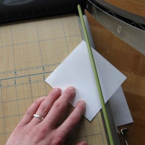 "photo of folded paper square about to be trimmed to 4"" down center"